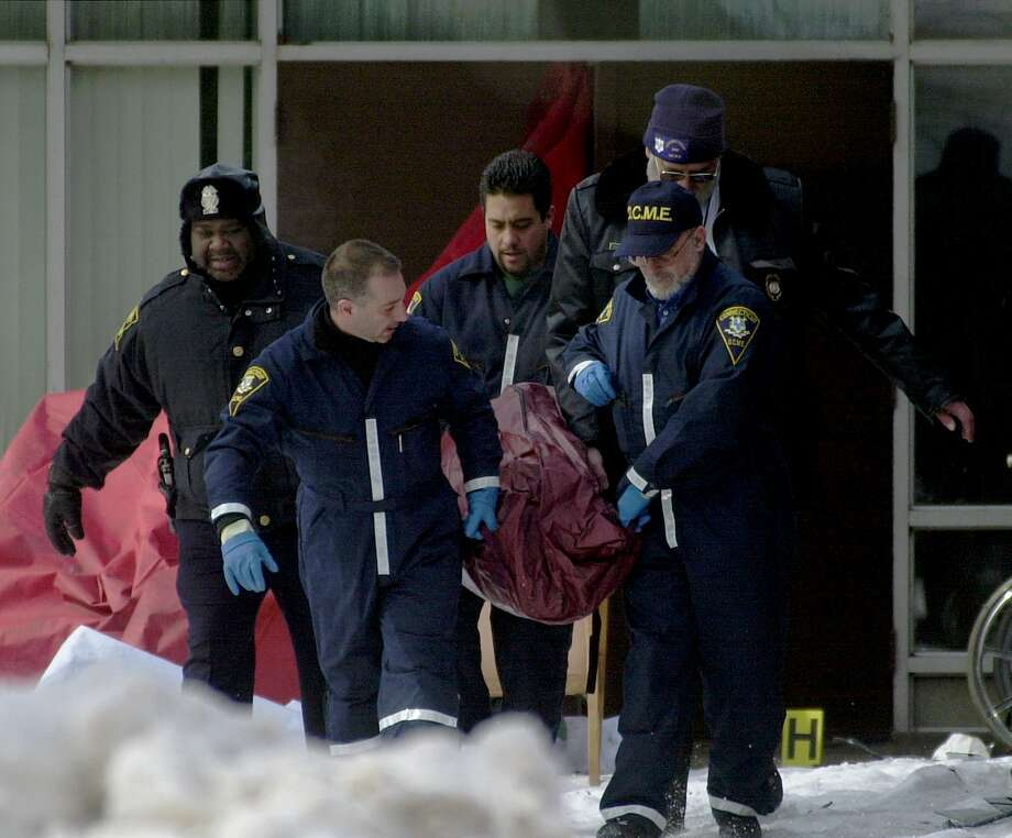 FILE - In this Feb. 26, 2003 file photo, state Medical Examiner's Office personnel and police remove a body from Greenwood Health Center in Hartford, Conn. A fire tore through the nursing home, killing 16 people. Tens of thousands of the country's most vulnerable people are living in nursing homes without adequate sprinklers or that are missing them altogether, according to government data as of July 2014. Despite a history of deadly nursing home fires and a five-year lead-up to an August 2013 deadline to install sprinklers, 385 facilities in 39 states licensed to house more than 52,000 people fail to meet requirements set by the Centers for Medicare and Medicaid Services. (AP Photo/Bob Child, File) ORG XMIT: MH205 Photo: Bob Child / AP