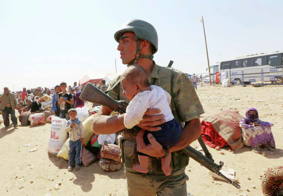A Turkish soldier holds a lost baby as he looks for its mother, as thousands of new Syrian refugees from Kobani arrive at the Turkey-Syria border crossing of Yumurtalik near Suruc, Turkey, Thursday, Oct. 2, 2014. (AP Photo/Burhan Ozbilici) ORG XMIT: XBO103 Photo: Burhan Ozbilici / AP