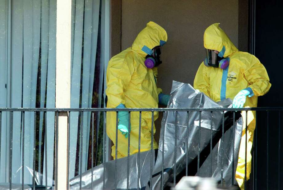 A hazardous materials crew prepares to enter the unit at Ivy Apartments where Thomas Duncan, a Liberian man who fell ill with Ebola, was staying with relatives, in Dallas, Oct. 3, 2014. After much delay, cleanup began at the the apartments Friday afternoon as workers scoured the property, taking any item that might harbor the virus. Health officials said Friday that they had identified 10 people who are most at risk of contracting Ebola after coming into contact with Duncan, now in isolation in a nearby hospital. (Cooper Neill/The New York Times) ORG XMIT: XNYT109 Photo: COOPER NEILL / NYTNS