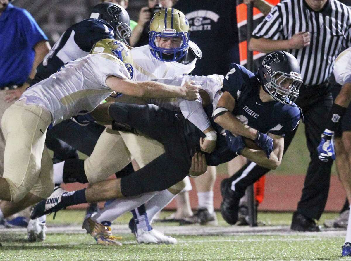 Boerne Champion's Cort Cowart (02) holds onto the ball while tackled by a trio of Kerrville Tivy defenders in Boerne on Friday, Oct. 3, 2014.