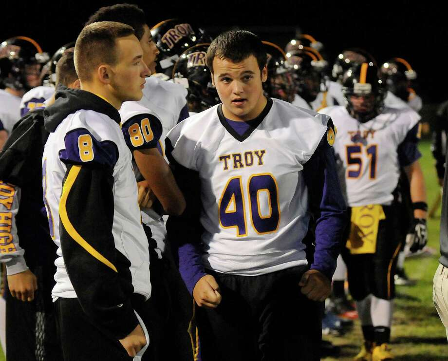 Troy's Zach Johnson (8) and Robert Taham (40) who along with other players who were suspended after a high school prank watch their teammates play against Bishop Maginn's during the first half of their Section II Class A football game on Friday, Oct. 3, 2014, in Albany, N.Y., (Hans Pennink / Special to the Times Union) ORG XMIT: HP101 Photo: Hans Pennink / Hans Pennink