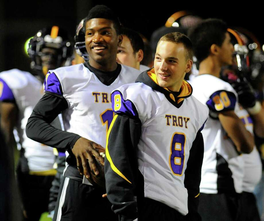 Troy's DaJuan Hudson (1) and Zach Johnson (8) who along with other players that were suspended after a high school prank react to media TV cameras as teammates play against Bishop Maginn's during the first half of their Section II Class A football game on Friday, Oct. 3, 2014, in Albany, N.Y., (Hans Pennink / Special to the Times Union) ORG XMIT: HP107 Photo: Hans Pennink / Hans Pennink