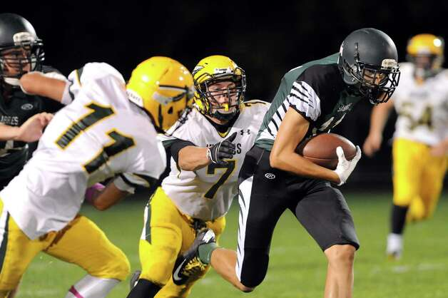 Schalmont's Zac O'Dell, right, carries the ball as Ravena's Jake Biernacki, center, defends during their football game on Friday, Oct. 3, 2014, at Schalmont High in Rotterdam, N.Y. (Cindy Schultz / Times Union) Photo: Cindy Schultz / 00028779A