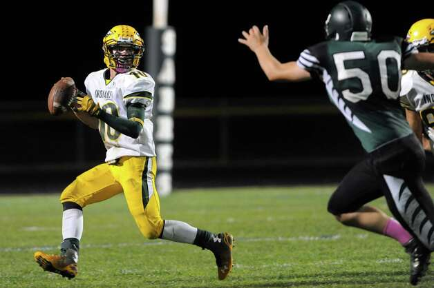 Ravena's quarterback David Warnken, left, looks to pass as Schalmont's  Matt Capovani gives pressure during their football game on Friday, Oct. 3, 2014, at Schalmont High in Rotterdam, N.Y. (Cindy Schultz / Times Union) Photo: Cindy Schultz / 00028779A