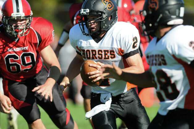 Schuylerville's quarterback William Griffen center, gains yards as Academy's Will Besch, left, defends during their football game on Friday, Oct. 3, 2014, at Albany Academy in Albany, N.Y. (Cindy Schultz / Times Union) Photo: Cindy Schultz / 00028780A