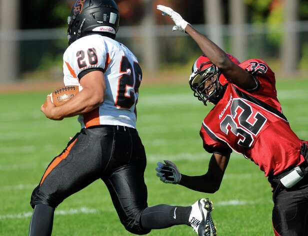 Schuylerville's Jacob Petrali, left, gains yards as Academy's Lamine Gueye defends during their football game against Academy on Friday, Oct. 3, 2014, at Albany Academy in Albany, N.Y. (Cindy Schultz / Times Union) Photo: Cindy Schultz / 00028780A