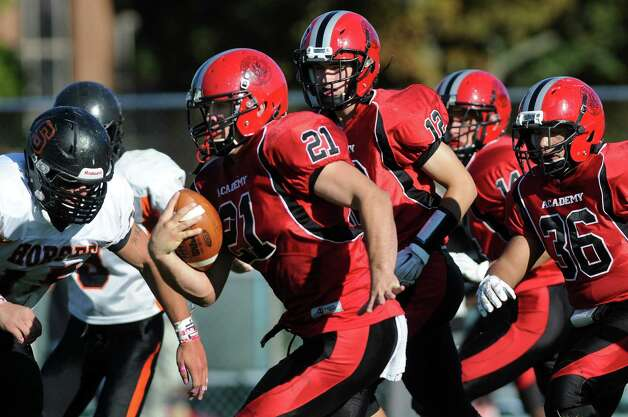 Academy's Dakota Harvey, center, gains yards during their football game against Schuylerville on Friday, Oct. 3, 2014, at Albany Academy in Albany, N.Y. (Cindy Schultz / Times Union) Photo: Cindy Schultz / 00028780A