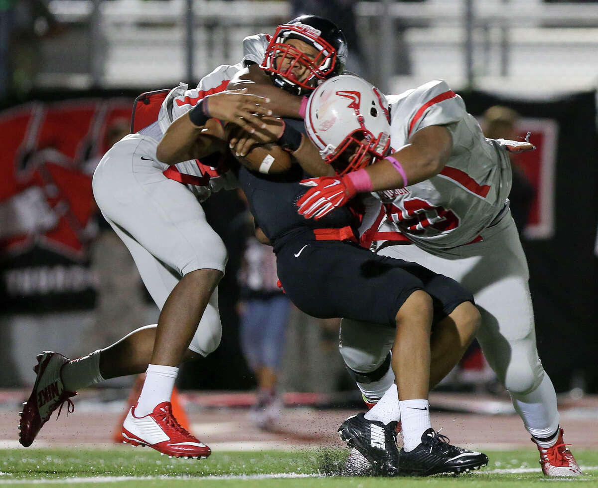 Judson's Alton Robinson (left) and Nigel Richardson (right) combine to bring down Wagner quarterback Jordan Batson for a loss during the second half of the