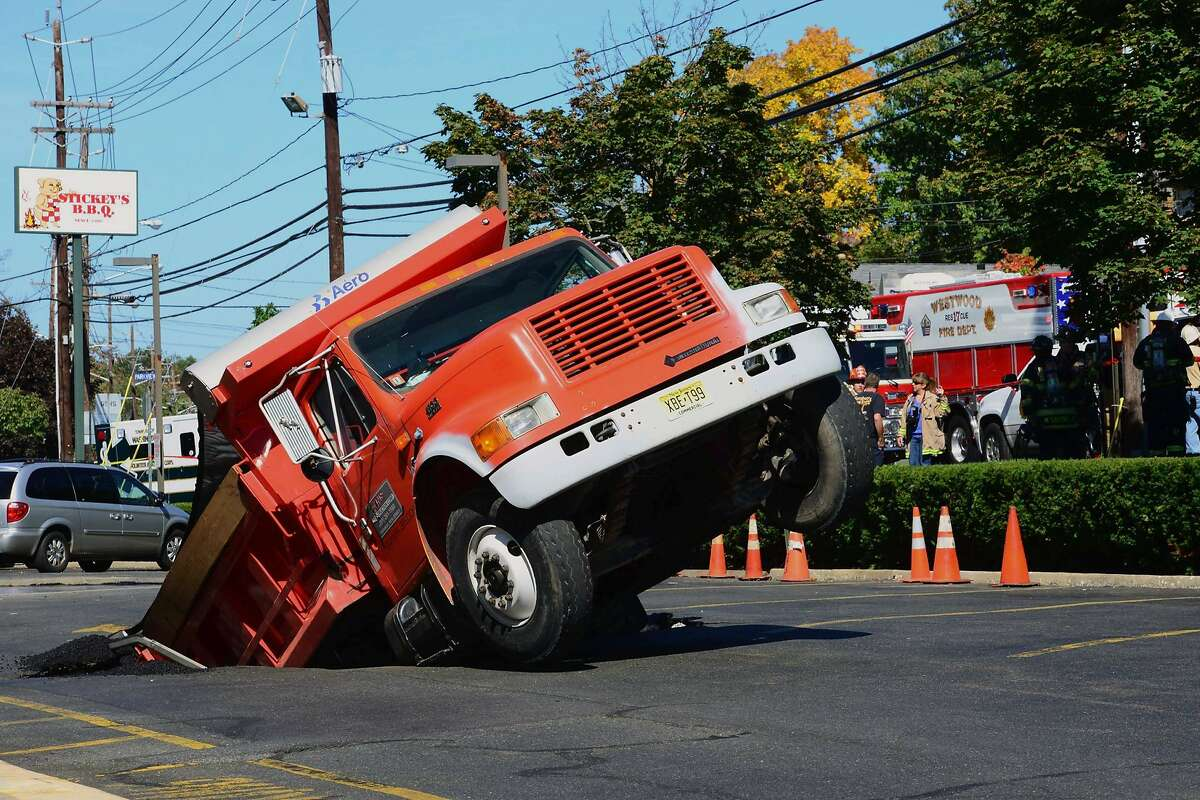 That sinking feeling: In Hillsdale, N.J., a dump truck making a delivery of asphalt discovers that the roof of an underground parking garage can't take the weight.