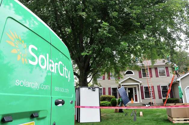 SolarCity installers put in a solar system on the roof of a home on Thursday, Oct. 2, 2014, in Schenectady, N.Y.  In total 41 panels were being installed on the home.   (Paul Buckowski / Times Union) Photo: Paul Buckowski / 00028865A