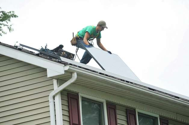 SolarCity installer Zack Bleau puts in a solar system on the roof of a home on Thursday, Oct. 2, 2014, in Schenectady, N.Y.  In total 41 panels were being installed on the home.   (Paul Buckowski / Times Union) Photo: Paul Buckowski / 00028865A