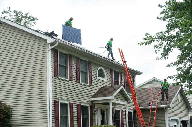 SolarCity installers, Zack Bleau, left, Steve Gowie II, center, and Brennan Willard put in a solar system on the roof of a home on Thursday, Oct. 2, 2014, in Schenectady, N.Y.  In total 41 panels were being installed on the home.   (Paul Buckowski / Times Union) Photo: Paul Buckowski / 00028865A
