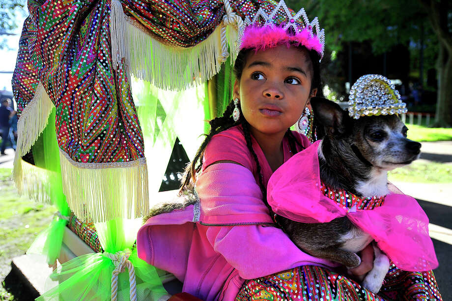 Maria Thomas, 6, takes in the activities as she and her dog Coco await the start of the opening parade of dogs during the annual Dogtoberfest event downtown Saturday. Celebrating all things canine, the event raises money for Beaumont Main Street.