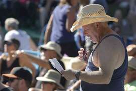 Duncan McCreight of San Francisco looks over a schedule during the second day of the Hardly Strictly Bluegrass Festival in San Francisco's Golden Gate Park Saturday, October 4, 2014.