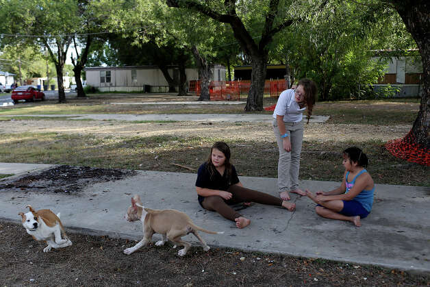 Labella Valenzuela, 9, from left, her sister, Valentina Valenzuela, 11, and neighbor Stephanie Perez, 7, play while Pinto, far left, and Cupcake, both dogs owned by neighbors, chase each other at the Mission Trails Mobile Home Park in San Antonio on Tuesday, Sept. 16, 2014. Photo: Lisa Krantz / SAN ANTONIO EXPRESS-NEWS