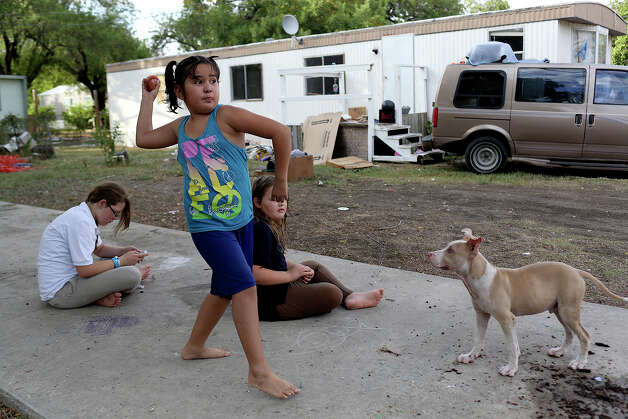 Stephanie Perez, 7, throws a ball for Cupcake, a neighbor's dog, while Valentina Valenzuela,11, left, and her sister, Labella Valenzuela, 9, entertain themselves outside the trailer their family was renting at the Mission Trails Mobile Home Park in San Antonio on Tuesday, Sept. 16, 2014. The sisters' family was supposed to leave the park that day but they did not have a place to move to. Photo: Lisa Krantz / SAN ANTONIO EXPRESS-NEWS