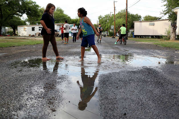 Labella Valenzuela, 9, left, and her neighbor, Stephanie Perez, 7, play at the Mission Trails Mobile Home Park in San Antonio on Tuesday, Sept. 16, 2014. Labella's family did not have a place to move to but they were supposed to move out that day. Photo: Lisa Krantz / SAN ANTONIO EXPRESS-NEWS