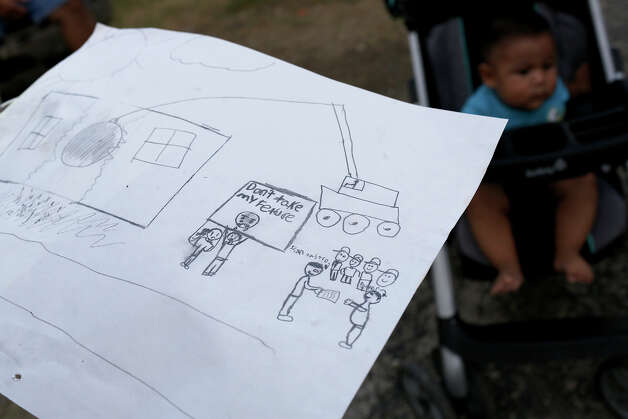 "Resident Irvin Garcia, 12, drew a picture from a dream he had a few nights earlier about his family being forced to move from their home at the Mission Trails Mobile Home Park in San Antonio. Garcia said he woke up at midnight and drew the picture. ""I felt this was my trailer,"" Garcia said, of wrecking ball hitting his home on Tuesday, Sept. 16, 2014. At right is Daniel De La Cruz, six months, who's family does not have the means to move their trailer either. Photo: Lisa Krantz / SAN ANTONIO EXPRESS-NEWS"