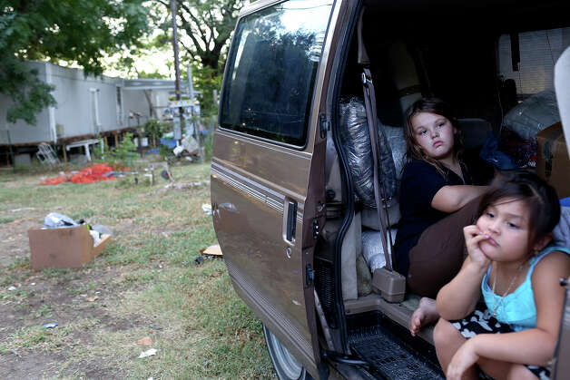 Labella Valenzuela, 9, sits in her family's van, packed with some of their belongings, outside the trailer home her family was renting at the Mission Trails Mobile Home Park in San Antonio on Tuesday, Sept. 16, 2014. The family did not have a place to move to but they were supposed to move out that day. At right is neighbor Sarai Guzman, 5. Photo: Lisa Krantz / SAN ANTONIO EXPRESS-NEWS