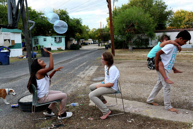 Itzel Cordova, 13, left, and Valentina Valenzuela, 11, play with a balloon while Juan Cordova, 16, carries his sister, Sarai Guzman, 5, to their trailer at the Mission Trails Mobile Home Park in San Antonio on Tuesday, Sept. 16, 2014. Photo: Lisa Krantz / SAN ANTONIO EXPRESS-NEWS
