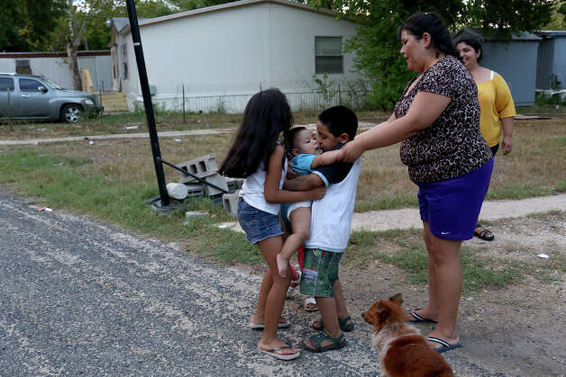 Oneyda Perez, right, keeps watch as her daughter, Sophia De La Cruz, 8, left, and their neighbor, Andres Bonilla, 6, embrace her son, Daniel De La Cruz, six months, at the Mission Trails Mobile Home Park in San Antonio on Tuesday, Sept. 16, 2014. Photo: Lisa Krantz / SAN ANTONIO EXPRESS-NEWS