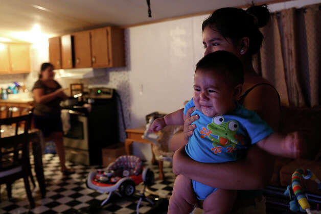 Katia De La Cruz, 13, holds her brother, Daniel De La Cruz, six months, in their home at the Mission Trails Mobile Home Park in San Antonio on Tuesday, Sept. 16, 2014. The family of six has poured thousands into improving their mobile home but don't have a place they can afford  to move it to. Photo: Lisa Krantz / SAN ANTONIO EXPRESS-NEWS
