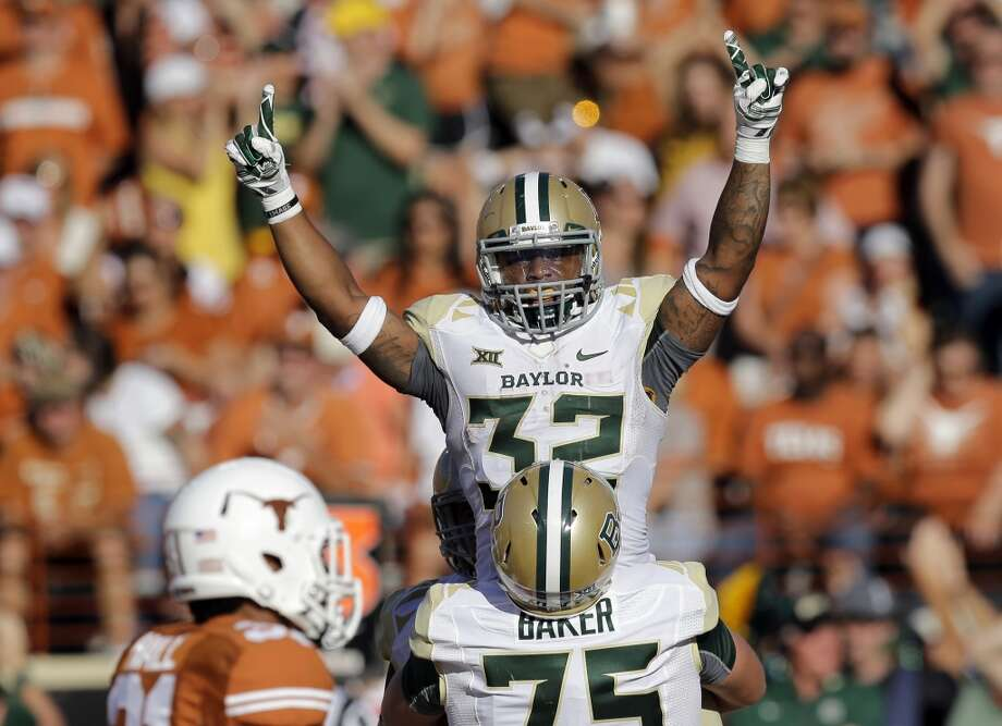 Baylor's Shock Linwood (32)  is lifted by teammate Troy Baker after he scored a touchdown against Texas during the second half of an NCAA college football game, Saturday, Oct. 4, 2014, in Austin, Texas. (AP Photo/Eric Gay) Photo: Eric Gay, Associated Press