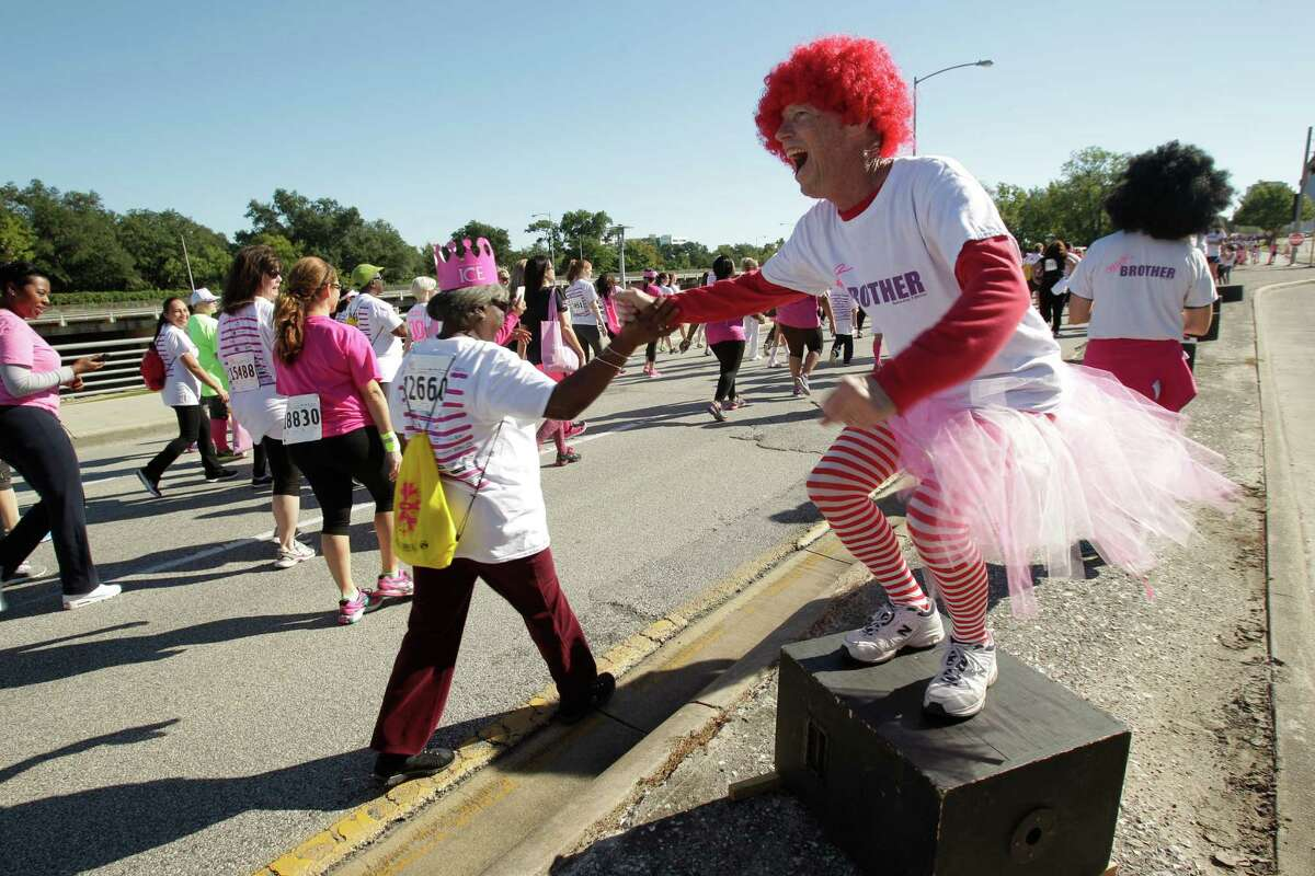 Brother Peter cheers on walkers along Allen Parkway during the 2014 Susan G. Komen Race for the Cure on Saturday, Oct. 4, 2014, in Houston.