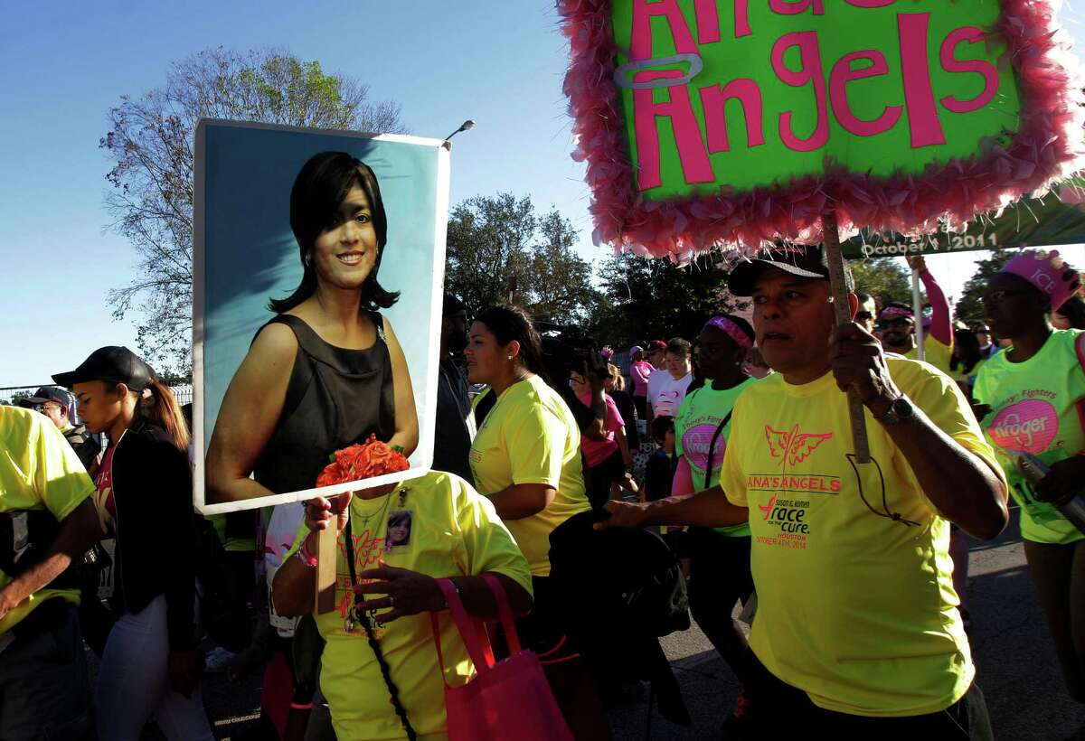 Consuelo Barron carries a photo of daughter Ana Barron Garcia who passed away while husband John Barron walks behind her during the 2014 Susan G. Komen Race for the Cure on Saturday, Oct. 4, 2014, in Houston.