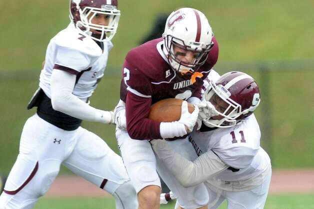Union's Andrew Baker, center, carries the ball as Springfield's Max Ford defends during their football game on Saturday, Oct. 4, 2014, at Union College in Schenectady, N.Y. (Cindy Schultz / Times Union) Photo: Cindy Schultz / 10028825A