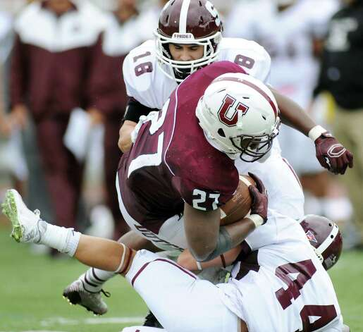 Union's Darnel Thomas, center, can't fight off a tackle from Springfield's Joey Racciopi during their football game on Saturday, Oct. 4, 2014, at Union College in Schenectady, N.Y. (Cindy Schultz / Times Union) Photo: Cindy Schultz / 10028825A