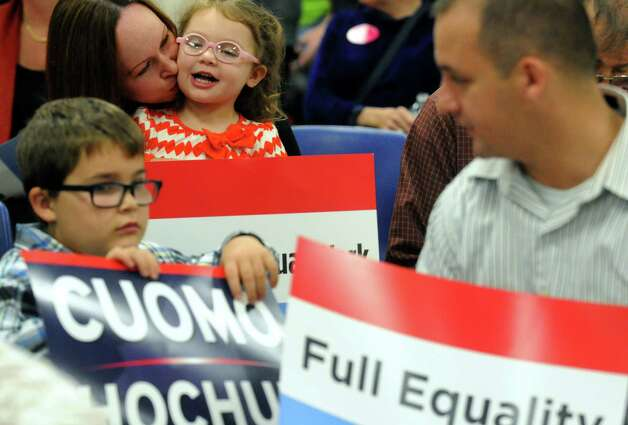 Kelly Brady of Cohoes, left, gives her two-year-old daughter Addison Brady a kiss during a rally to build support for the women's equality agenda at the Albany Labor Temple on Saturday Oct. 4, 2014 in Albany, N.Y.  (Michael P. Farrell/Times Union) Photo: Michael P. Farrell / 00028882A