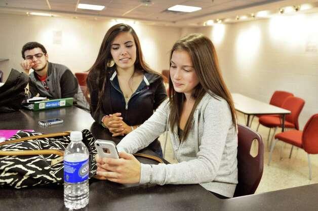 Seniors, from left, Jonathan Mennato, Claudia Mungnia, and Rachel Olockiuse their cell phones in the student commons at Niskayuna High School Friday Sept. 26, 2014, in Niskayuna, NY.  (John Carl D'Annibale / Times Union) Photo: John Carl D'Annibale / 00028756A