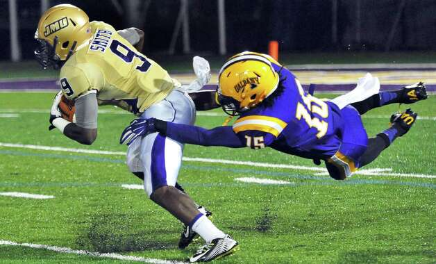 UAlbany's #15 Rayshan Clark, right, hangs on to James Madison's #9 DeAndre Smith during Saturday's Colonial Athletic Association game at University at Albany's Bob Ford Field Oct. 4, 2014, in Albany, NY.  (John Carl D'Annibale / Times Union) Photo: John Carl D'Annibale / 00028860A