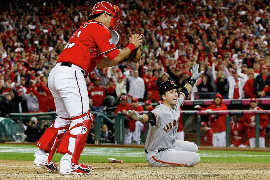 San Francisco Giants' Buster Posey signals to the umpire he's safe after sliding into home in the ninth inning of Game 2 of baseball's NL Division Series at Nationals Park, Saturday, Oct. 4, 2014, in Washington. The umpires ruled, after review, that Washington Nationals catcher Wilson Ramos, left, made the tag and Posey was out. (AP Photo/Alex Brandon) ORG XMIT: NAT135 Photo: Alex Brandon / AP