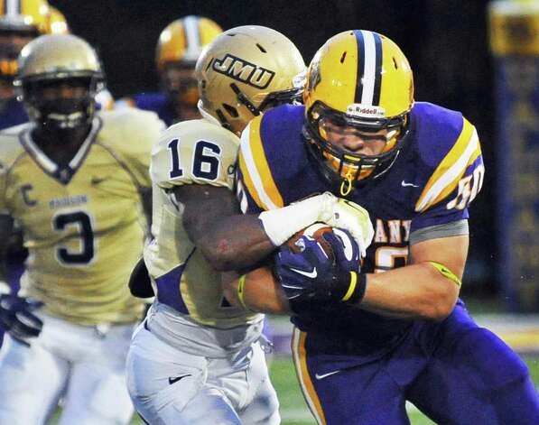 UAlbany's #80 Brian Parker, right, holds tight to the ball as he's brought down by James Madison's #16 Dean Marlowe during Saturday's Colonial Athletic Association game at University at Albany's Bob Ford Field Oct. 4, 2014, in Albany, NY.  (John Carl D'Annibale / Times Union) Photo: John Carl D'Annibale / 00028860A