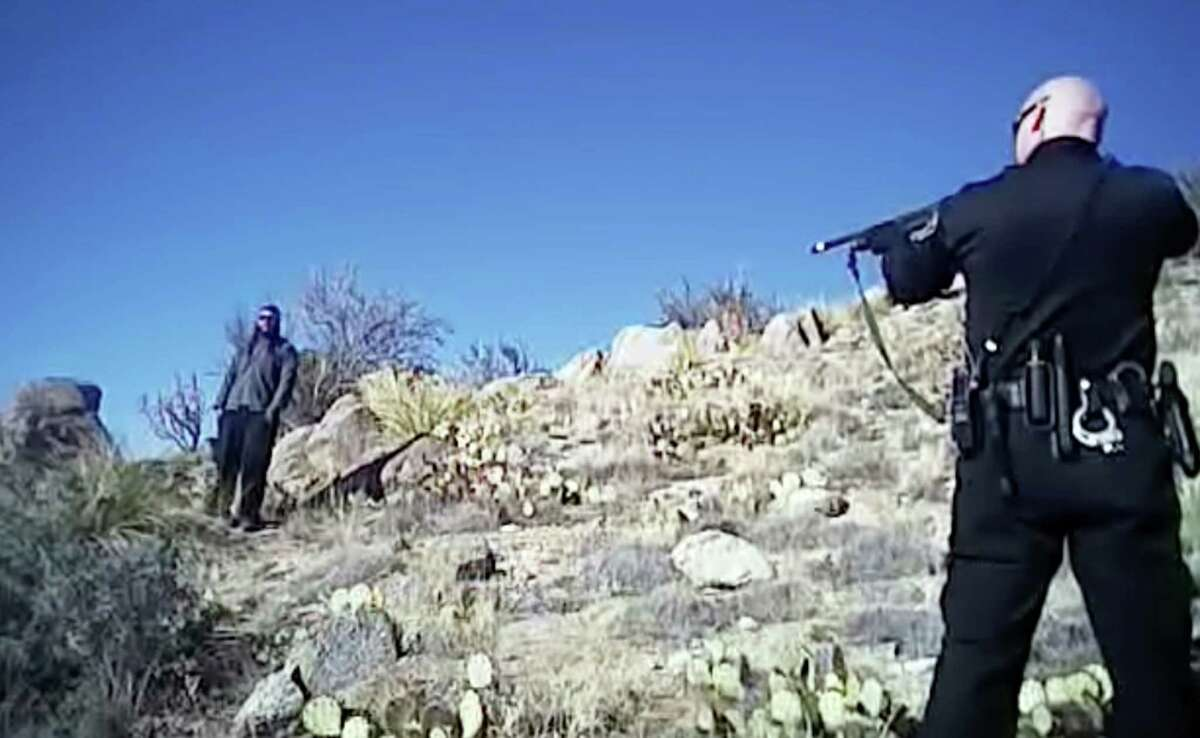 In this file photo taken from a video shot March 16, 2014, James Boyd, 38, left, is shown during a standoff with officers in the Sandia foothills in Albuquerque, N.M., before police fatally shot him. An Albuquerque police officer's comments and behavior before a fatal shooting that sparked a protest and FBI investigation were