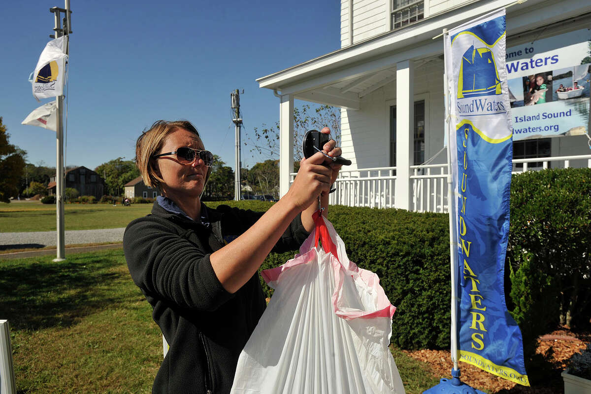 A volunteer measures how much trash she picked up after helping to clean up a beach on Long Island Sound in Stamford.