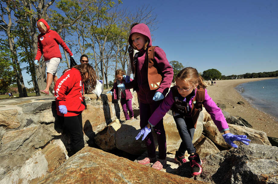 Friends and family members of Brownie Troop #50444 volunteer to pick up trash during International Coastal Cleanup Day at Cove Island Park in Stamford, Conn., on Sunday, Oct. 5, 2014. Over 640,000 volunteers world-wide were estimated to take part in the effort. At Cove Island Park alone, SoundWaters recorded 83 volunteers picked up a total of 229 pounds of trash. The top three items volunteers picked up at the park: nearly 1,500 bottle caps (plastic and metal), over 900 food wrappers and over 800 cigarette butts, among many other items. Photo: Jason Rearick / Stamford Advocate