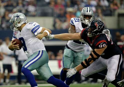 Dallas Cowboys quarterback Tony Romo (9) rolls out as Houston Texans defensive end J.J. Watt (99) pursues during the first half of an NFL football game, Sunday, Oct. 5, 2014, in Arlington, Texas. (AP Photo/Tim Sharp) Photo: Tim Sharp, Associated Press / FR62992 AP