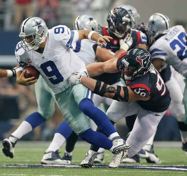 Dallas Cowboys quarterback Tony Romo (9) is nearly sacked by Houston Texans defensive end J.J. Watt (99) but was able to recover and and throw a touchdown during the third quarter of an NFL football game at AT&T Stadium, Sunday, Oct. 5, 2014, in Arlington. Photo: Karen Warren, Houston Chronicle / © 2014 Houston Chronicle