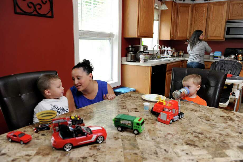 Jessica Regan, 32, left, with son Caden, 3, and Donovan Reklaitis, 2 1/2, have some snacks during a Mom's Club meeting at the home of Allison Reklaitis in Danbury, Conn. Tuesday, Sept. 30, 2014. Photo: Carol Kaliff / The News-Times