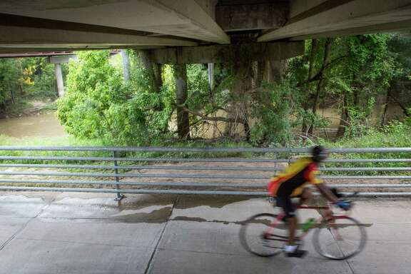 A cyclist speeds on a bike trail that passes under Eldridge Parkway on The Energy Corridor District in Houston. The area has more than 50 miles of scenic trails for bicycles and pedestrians. Monday, Sept. 22, 2014, in Houston.