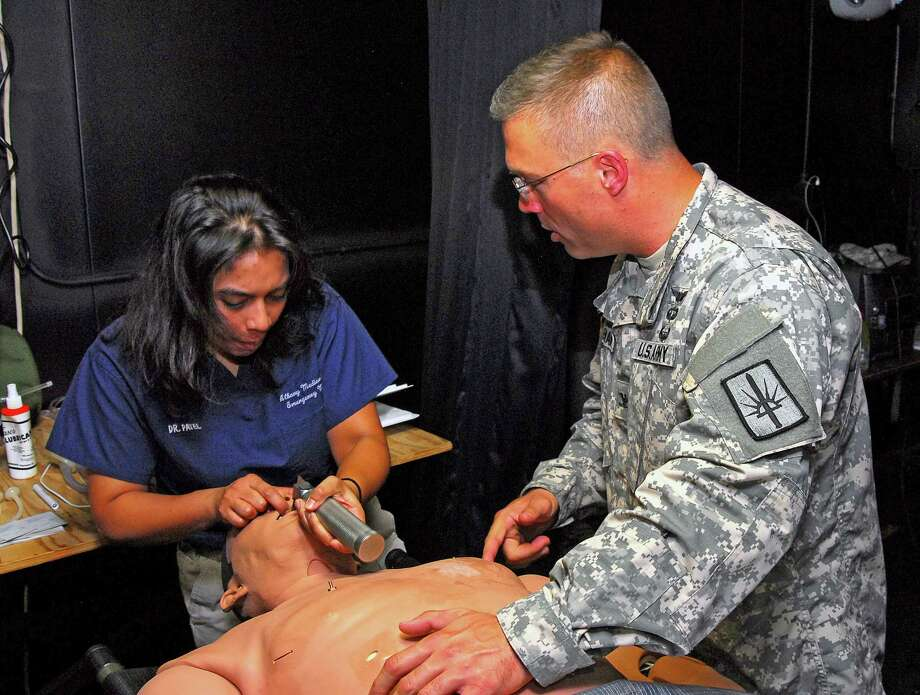 CAMP SMITH TRAINING SITE, Cortlandt Manor -- Dr. Anar Patel, a resident doctor from Albany Medical Center, slowly works a laryngoscope through the throat of a mannequin in order to open the air passage and place an endotracheal tube into the lungs so that bag-mask ventilator can be applied to assist the patient?s breathing while Col. James Coleman, the newly appointed state surgeon looks on. Patel and another resident doctor were on hand at Camp Smith during the medical command?s annual training.  The doctors were invited to come to Camp Smith on Aug. 5 to become familiar with the Army methods and procedures of operating a field aid station and to give some professional guidance to all New York Army National Guard medics who wanted to perfect their life-saving skills. Photo: SFC Steven Petibone