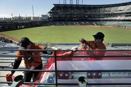 Members of the stadium operations crew tape up decorative plastic wrap on a balcony in centerfield at AT&T Park in San Francisco, on Sunday, October 5, 2014, as the Giants prepared to play the Washington Nationals in Game 3 of the National League Division Series the following day.
