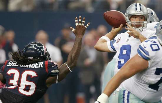 Dallas Cowboys quarterback Tony Romo (9) looks for an open teammate as Houston Texans strong safety D.J. Swearinger (36) defends during the first half of an NFL football game against the Houston Texans, Sunday, Oct. 5, 2014, in Arlington, Texas. Dallas won 20-17 in overtime. (AP Photo/Brandon Wade) Photo: Brandon Wade, Associated Press / FR168019 AP
