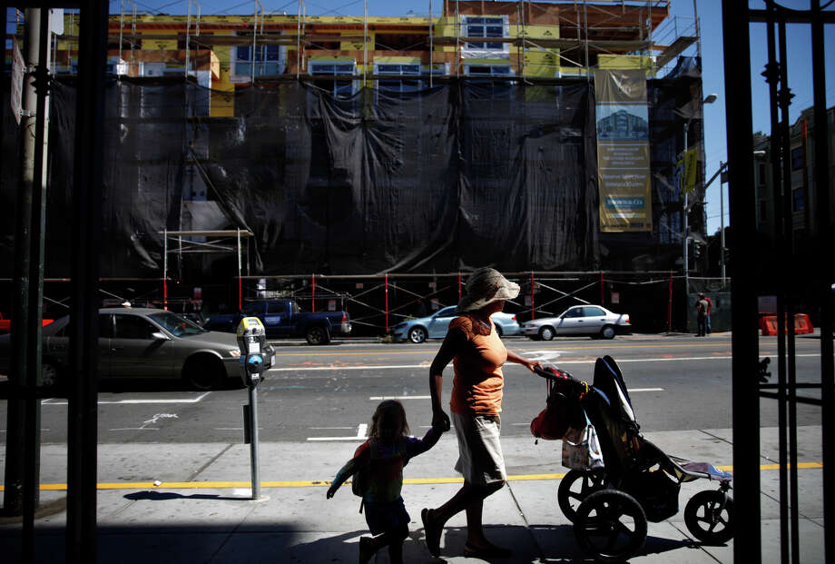 Pedestrians walk along Valencia Street across from a new construction project which had been a parking lot and gas station in San Francisco. Photo: Lea Suzuki / The Chronicle / ONLINE_YES