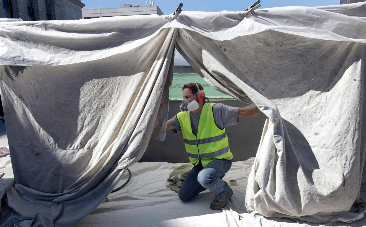 Randy Montgomery prepares the area before sandblasting an inscription onto the memorial.