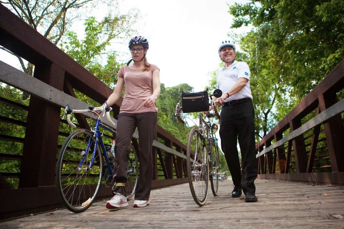 Kelly Rector and Clark Martinson, officials with the Energy Corridor District, walk their bicycles last fall along part of the 50 miles of scenic trails the district has in Houston.