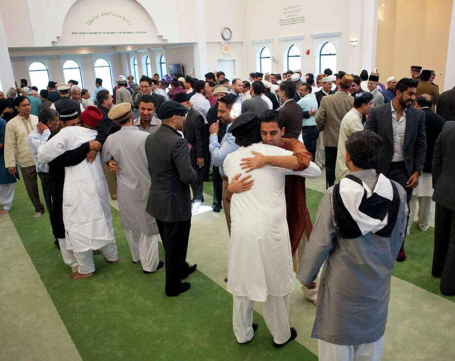 Ahmadiyya Muslim men embrace after the Eid al-Adha prayer and sermon at the Baitul Samee Mosque in north Harris County on Sunday where they honored sacrifices. The sect is outlawed in Pakistan. Photo: Alysha Beck, Freelancer / Houston Chronicle